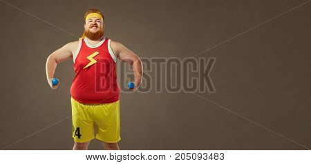 A funny bearded fat man smiles in sports clothes with small dumbbells.
