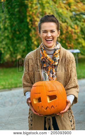Woman On Halloween Outdoors Showing Carved Pumpkin