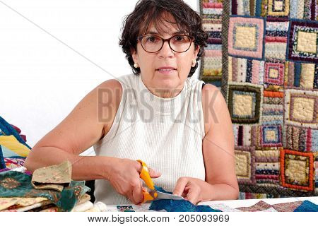 a smiling mature seamstress cutting the fabric