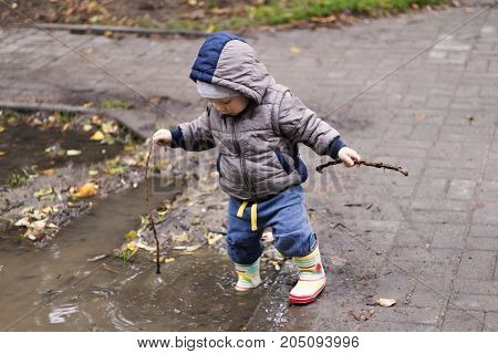 Cute one year toddler dressed in boots and rubber pants jumping in a puddle. Funny kid with children's happiness