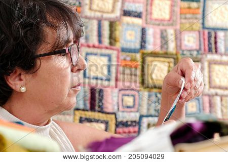 a portrait of a mature seamstress with glasses