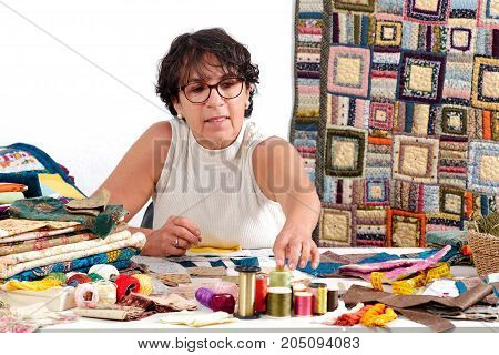 a mature brunette woman sewing a  patchwork