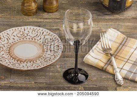 fork and knife on red napkin and wine glasses background A glass of wine on a wooden background table, with a plate with a fork. A bottle of wine and accessories