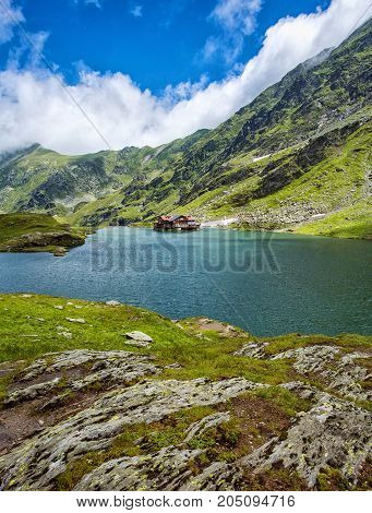 Mountain lake. The lake between the rocks. Hotels on the shore. Artistic picture. Eastern Europe. Romania. Lake Balea. Typical alpine house on mountain lake. Beautiful blue sky with clouds.