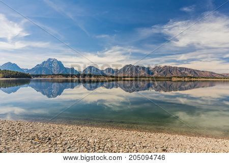 a scenic reflection of the Tetons in fall in Jackson lake