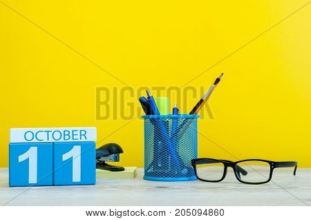 October 11th. Day 11 of month, wooden color calendar on teacher or student table, yellow background . Autumn time. Empty space for text.