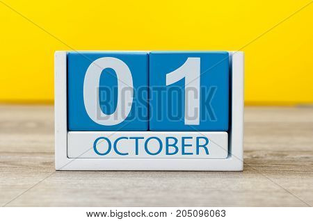 October 1st . First day, October 1 blue wooden calendar on yellow abstract background. Autumn day.