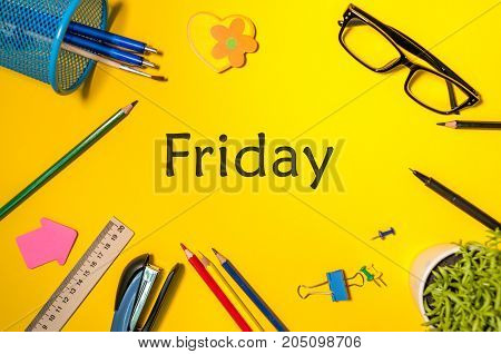 Friday on yellow table background with pencil, glasses and other office supplies. Business day concept.