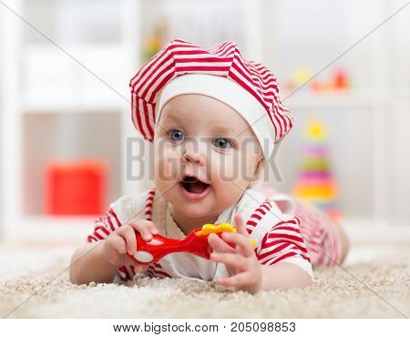 baby lying on the floor and plays with toy indoor