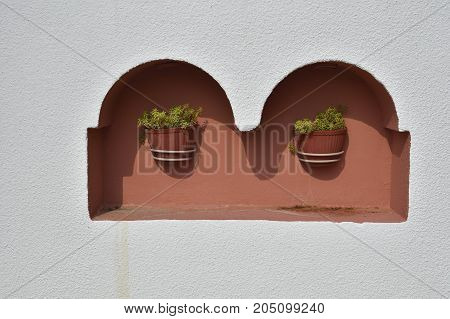 Two flowerpots with flowers in a niche on a house facade picture from the North of Greece.