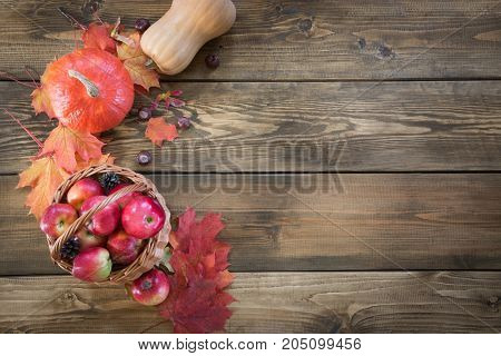 Autumn harvest, pumpkin, apples in basket, colorful autumn leaves on wooden board. Fall still life, vintage style. Top view.