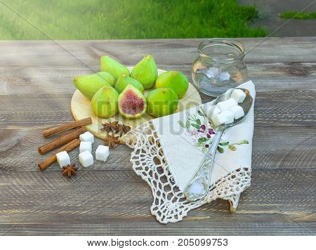 Fresh green figs, jam cooking process. Still life with figs on wooden background, surrounded by spices, embroidered napkin, vintage spoon. Sugar, spices, notebook for recipes, rustic wooden background.