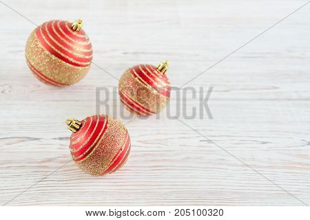 Three red christmas balls on white wooden background. Christmas and New Year concept. Copy space background