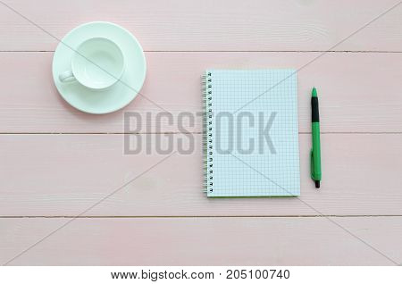 Open notebook with green pen and coffee cup on pink wooden background. Copy space background top view flat lay overhead