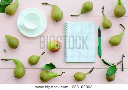 Open notebook with green pen coffee cup and pears on pink wooden background. Top view flat lay overhead