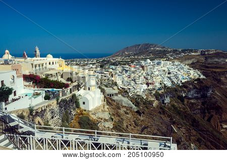 Fira, Thira town, Santorini Cyclade islands, Greece. Beautiful view of the town with white buildings blue church's roofs and many colored flowers.
