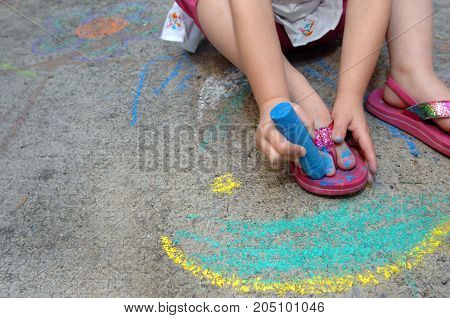 Little girl paints her toe nails blue with the help of some sidewalk chalk showiing creativity and thinking outside the box.