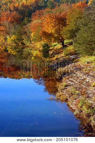 Glassy surface of river reflects the brilliant color of the Fall foliage in Northern Arkansas.