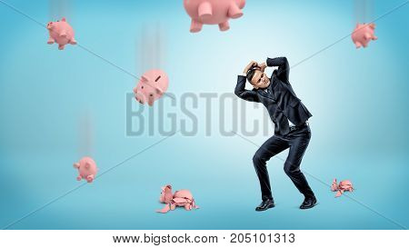 A businessman hides his head from many piggy banks that fall down and crack at the floor. Unwanted banking plan. What to do with money. Finance management.