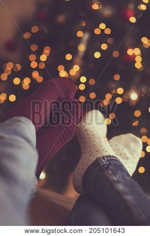 Detail of male and female feet wearing warm winter socks placed on the table with Christmas tree and Christmas lights in background. Selective focus