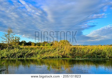 Colorful autumn landscape with a river and clouds.
