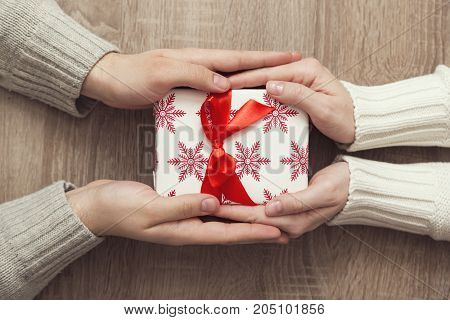 Top view of a couple exchanging Christmas presents and holding hands
