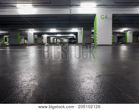 The gray car parked in the parking lot. The car park is dark and lonely in the mall.