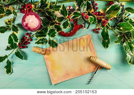 An overhead photo of a piece of old paper with a place for text, a cork, and a corkscrew, on a teal background with a burning candle and holly branches, a Christmas or New Year greeting card template