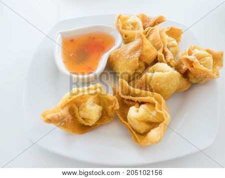 Deep fried wonton with the chili sweet sauce on the white plate.