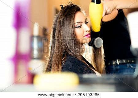 Hairdresser dries hair with a hairdryer in beauty salon