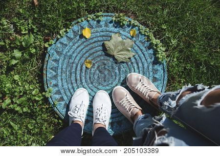 Two pairs of woman's legs and fallen leaves on manhole. Top view. Lifestyle concept