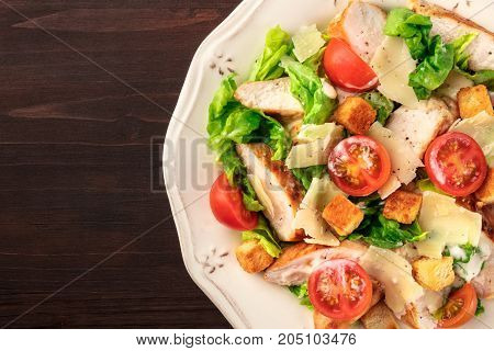 An overhead closeup photo of a plate of chicken Caesar salad with cherry tomatoes on a dark rustic background texture with copy space