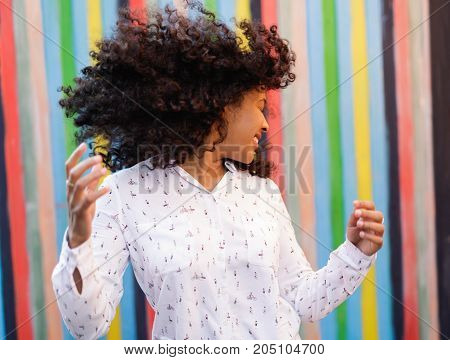Dancing woman with hair blow at colorful wall