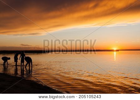 Silhouette of kids playing on the beach water's edge during sunset. Silhouette outlines modified to render persons unidentifiable.