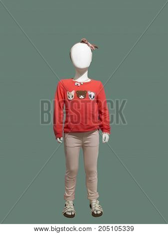 Full-length child mannequin dressed in casual clothes isolated on green background. No brand names or copyright objects.