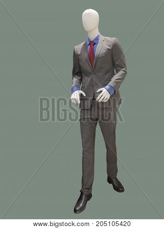 Full-length male mannequin dressed in gray suit isolated. No brand names or copyright objects.