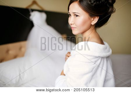A bride in a white robe from the morning before putting on a wedding dress on a wedding day.