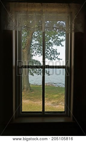 A window in the historic Pointe aux Barques Lighthouse at the tip of Michigan's thumb frames a glimpse of its grounds and Lake Huron beyond. Port Hope, Michigan.