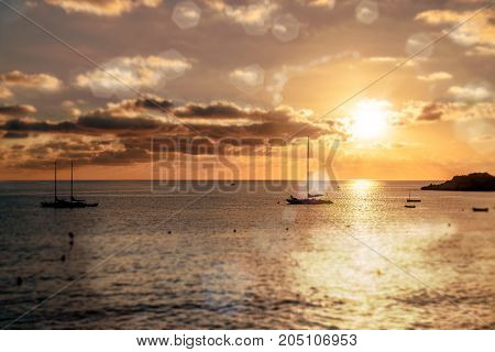 Magnificent sunset above the Mediterranean Sea and sailboats silhouette. Ibiza Spain