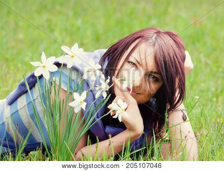 Young beautiful woman lying on the grass and posing with white daffodils. Spring time photo.