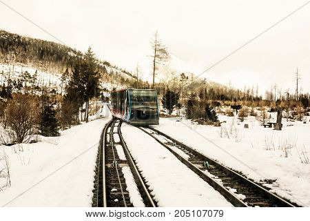 Funicular railway at High Tatras mountains in Slovak republic. Rail cable car leads from Stary Smokovec to ski and tourist resort Hrebienok. Yellow photo filter.