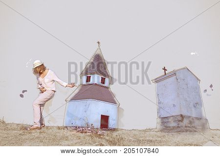 Young caucasian woman imitates guitar playing by the church on the hill. Sketch scene. Art technique. Retro photo filter.