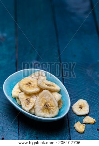 Dried Banana In A Bowl On Petrol Colored Wooden Background
