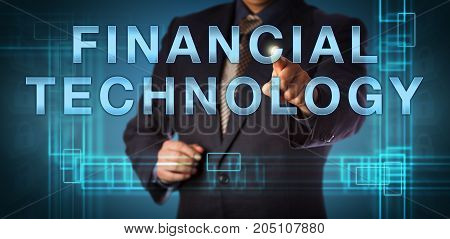 Unrecognizable corporate manager is pointing at FINANCIAL TECHNOLOGY on a touch screen. Business and IT concept for FinTech and financial services provided as end to end process via the internet.