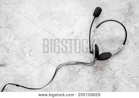 Call center manager's accessories. Headphones on gery background top view.