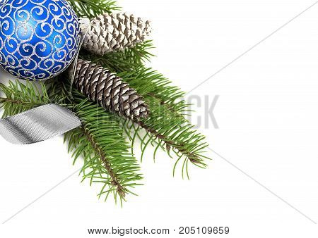 Christmas decoration of blue ball with cones and fir tree branch and silver ribbon isolated over white background