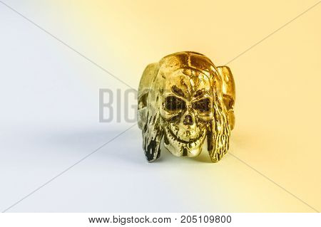 Silver Skull Ring On A Light Yellow Background.