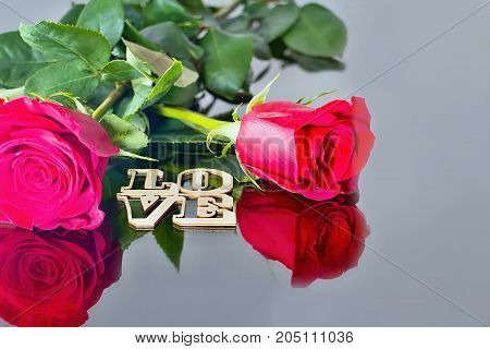 Red roses with reflection in the mirror and the inscription: LOVE. For lovers. Roses heart leaves and mirror. Romantic atmosphere.