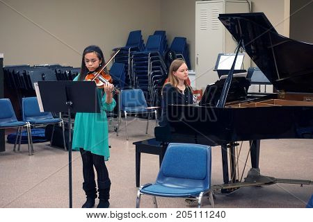 ROMEOVILLE, ILLINOIS / UNITED STATES - MARCH 5, 2016: A young violinist performs in a student recital at Lewis University.