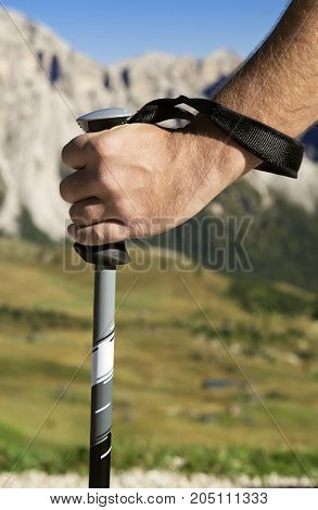 Close-up of a hand with walking pole against mountain in the distance